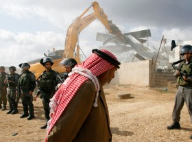 A Palestinian man walks past Israeli border police standing guard as a bulldozer demolishes a structure in the West Bank village of Beit Hanina, near Jerusalem November 24, 2011. Two structures, built without permits, were razed by the Israeli army and civil administration on Thursday after three years of reviews and deliberations in a construction committee, a civil administration spokesperson said. REUTERS/Mohamad Torokman (WEST BANK - Tags: POLITICS CIVIL UNREST) - RTR2UERH