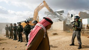 A Palestinian man walks past Israeli border police standing guard as a bulldozer demolishes a structure in the West Bank village of Beit Hanina
